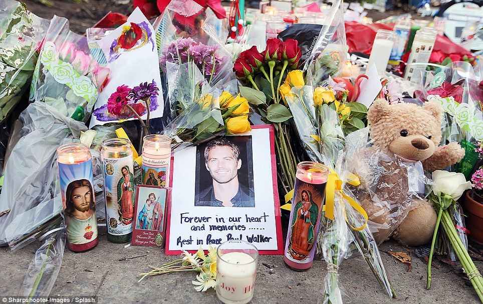 Fans gather and place flowers on Sunday at the scene of a fiery crash that killed Fast & Furious star Paul Walker in the Santa Clarita area of Los Angeles