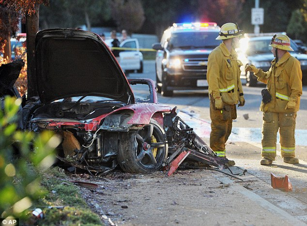First responders gather evidence near the wreckage of a Porsche sports car that crashed into a light pole on Hercules Street near Kelly Johnson Parkway in Valencia on Saturday, Nov. 30, 2013
