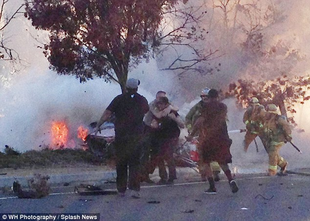 Tragic: This photo was taken just minutes after Walker's car crashed into a pole, and shows the Porsche in flames as fire marshals and police hold back friends who are trying to help