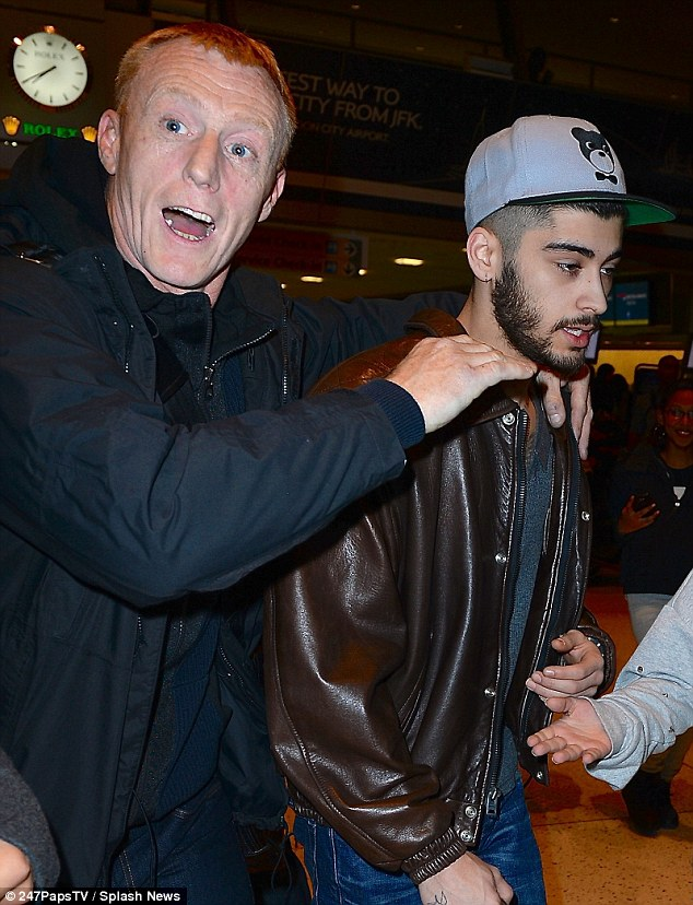 Cheer up: Zayn Malik fails to raise a smile as his bodyguard helps to get him through the crowded airport
