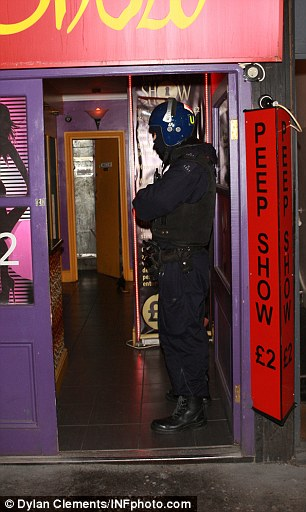 A officer in riot gear waits in the entrance of a sex-themed business