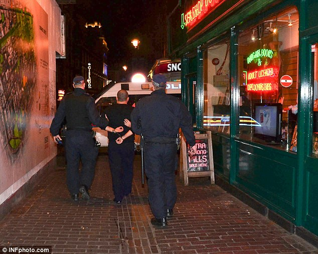Taken away: Police officers make an arrest as part of a major crackdown on drugs and human trafficking in Soho