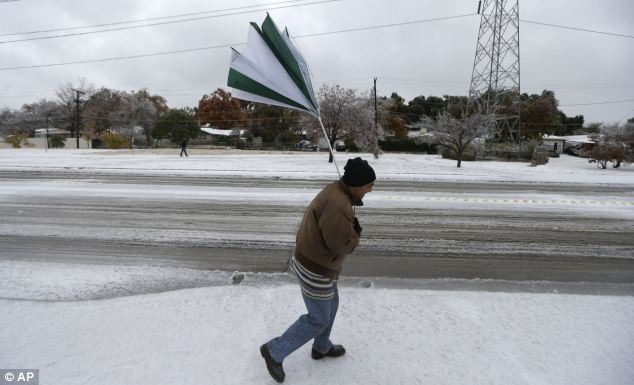 Blown away: A gust of wind collapses Joseph Mezo's umbrella as he walks to work in Dallas on Friday morning