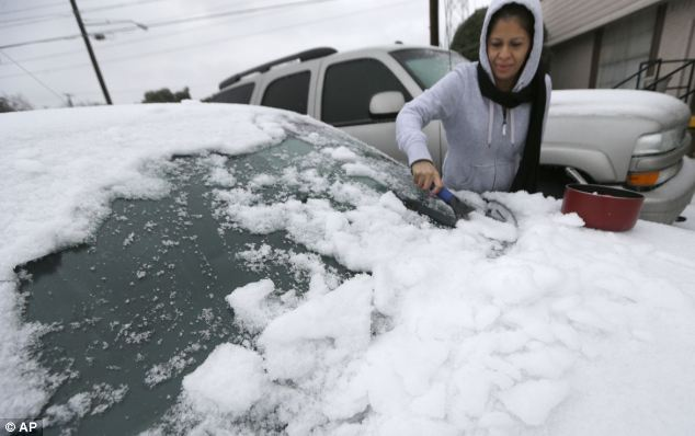 Cold snap: Laura Perez scrapes ice from her car as she prepares to drive to work in Dallas in icy conditions on Friday morning. The National Weather Service issued a winter storm warning for the area until Friday night