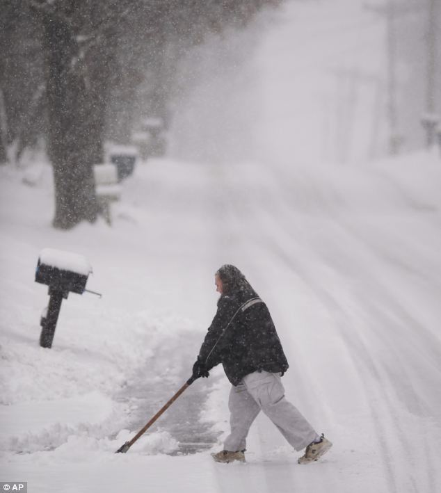 Storm: Christine Busik shovels her gravel driveway in Bloomington, Indiana during sleet and rain