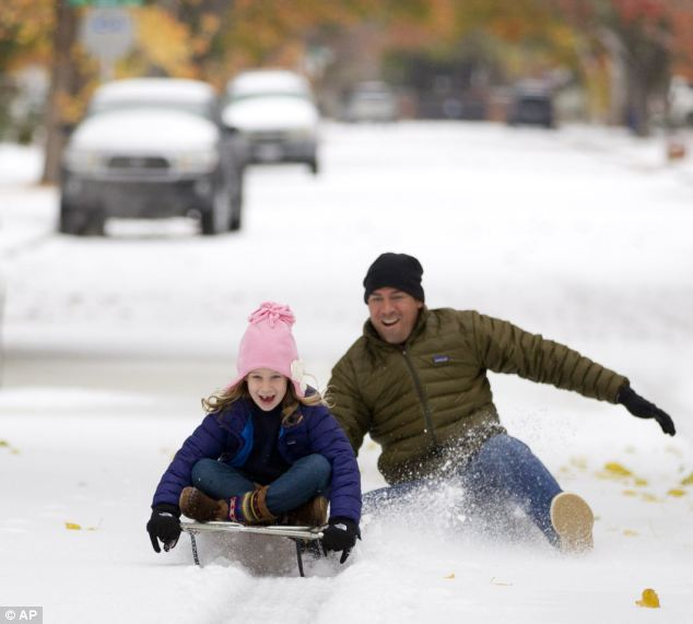 Enjoying it: Mark Vogel gives his daughter Parker, 7, a push on the sled he used when he was a kid on the icy streets in Fort Worth, Texas on Friday as temperatures plunged