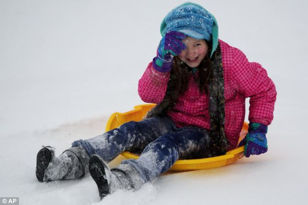 Joy: Jaidyn Richardson, 9, adjusts her hat after sledding down a hill at an Evansville, Indiana golf course