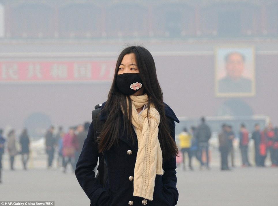 Citoyens: Cette femme portait un masque alors qu'elle se tenait dans emblématique de la place Tian'anmen de Beijing.  Les citoyens ont été dit de rester à l'intérieur plus tôt cette semaine et les constructeurs ont dû abandonner leurs postes