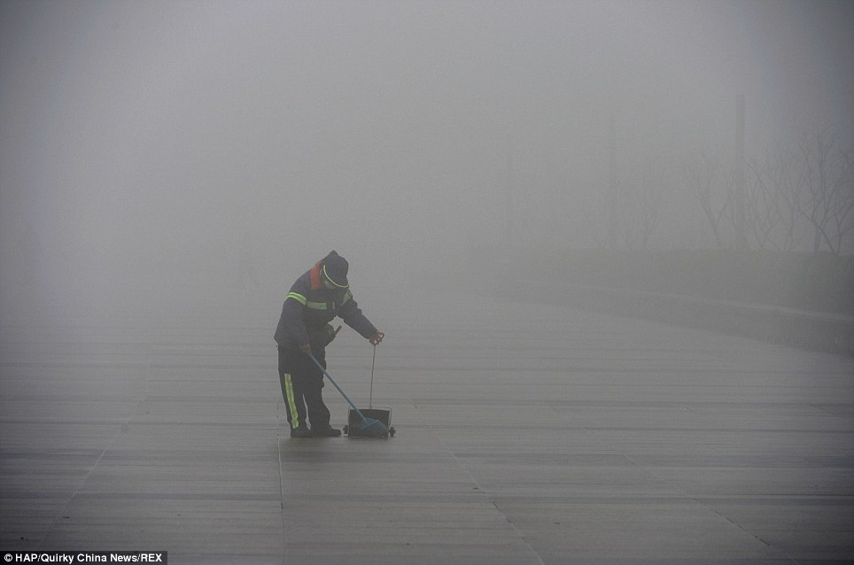 Bleak: Un nettoyeur de rue va à ses affaires dans le centre de Shanghai, en dépit de la pollution qui dépasse de loin règles de l'OMS - à près de 40 fois la limite en Janvier