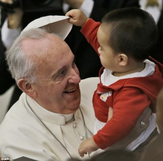 Oh look, it comes off: The child begins to remove the pontiff's zucchetto, or skullcap, during the Pope's tour of the paediatric centre