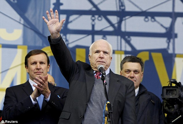 Greetings: U.S. Senator John McCain waves to pro-European integration protesters during a mass rally at Independence Square in Kiev