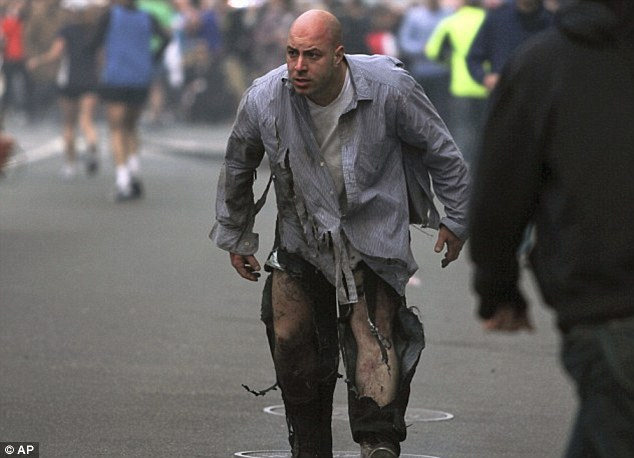 Pain: Costello is pictured in the streets moments after the blasts at the Boston Marathon finish line