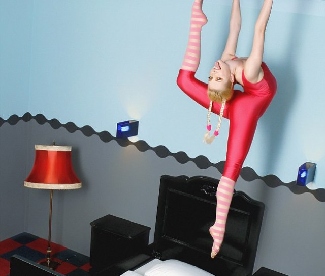 A View Of Snake Woman Zlata Jumping From A Bed And Bending Her Legs Behind Her
