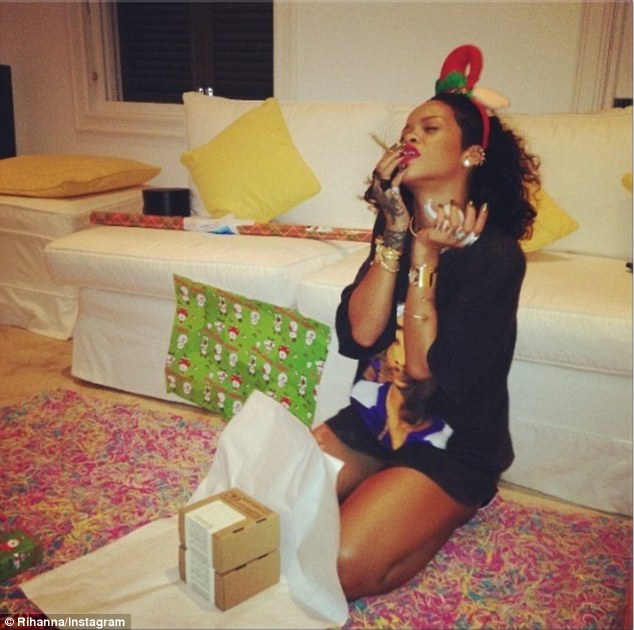 Christmas tradition: Rihanna shared this snap of herself smoking a roll up whilst listening to Mariah Carey songs and wrapping presents