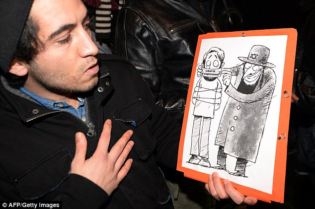 Political protest: A man poses with a drawing showing a Jew character covering the mouth of an other character with a gag reading 'freedom of speech' during a protest in support of Dieudonne