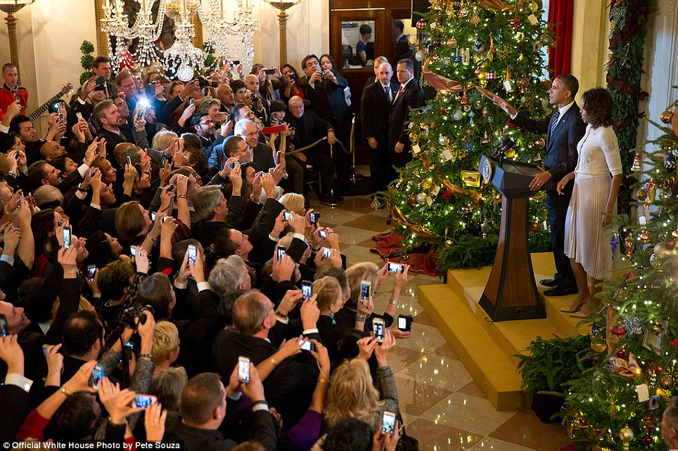 Everyone has a smart phone. The President delivers remarks with the First Lady during a Christmas reception in the Grand Foyer of the White House