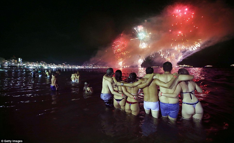 Brazilliant! Revellers embrace while watching fireworks explode along Copacabana Beach in Rio de Janeiro, where more than two million attended the celebrations