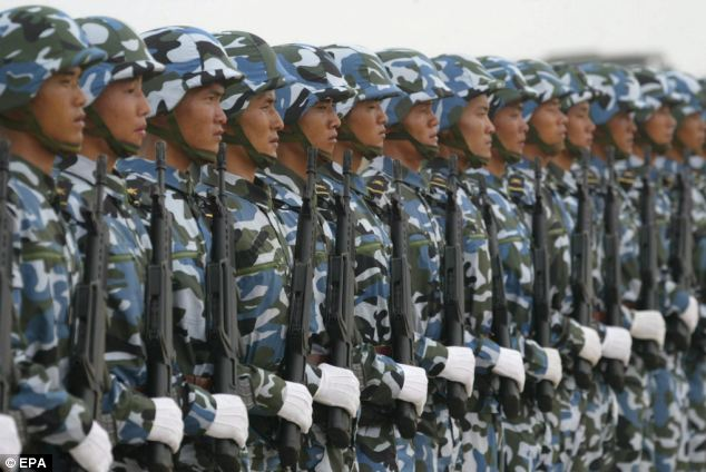 Armed Chinese soldiers stand at attention after being deployed in Qingdao, Shandong province