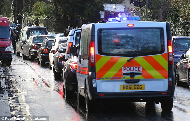 Escort: A police van and a row of cars follow the hearse to the funeral in north London