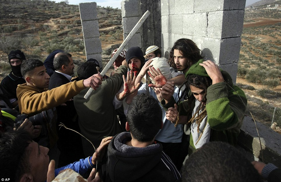 Palestinians confront Israeli settlers while others try to stop them before a group of settlers were detained by Palestinian villagers. They held more than a dozen Israeli settlers for about two hours on Tuesday in retaliation for the latest in a string of settler attacks on villages, witnesses said