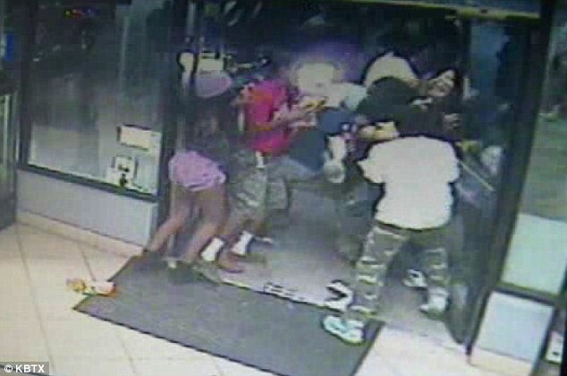 Mobbed: Store clerk Terry Polsgrove, 19, can be seen getting mobbed by the group as he desperately tried to close the door