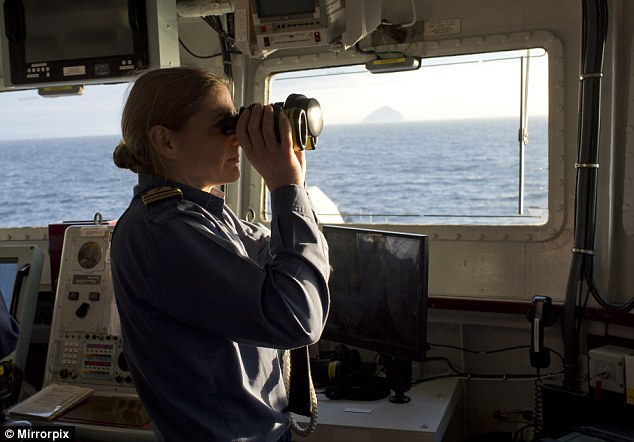 Cdr Sarah West looks through binoculars as the HMS Portland hunts a submarine in the Cumbrae Gap, Scotland.