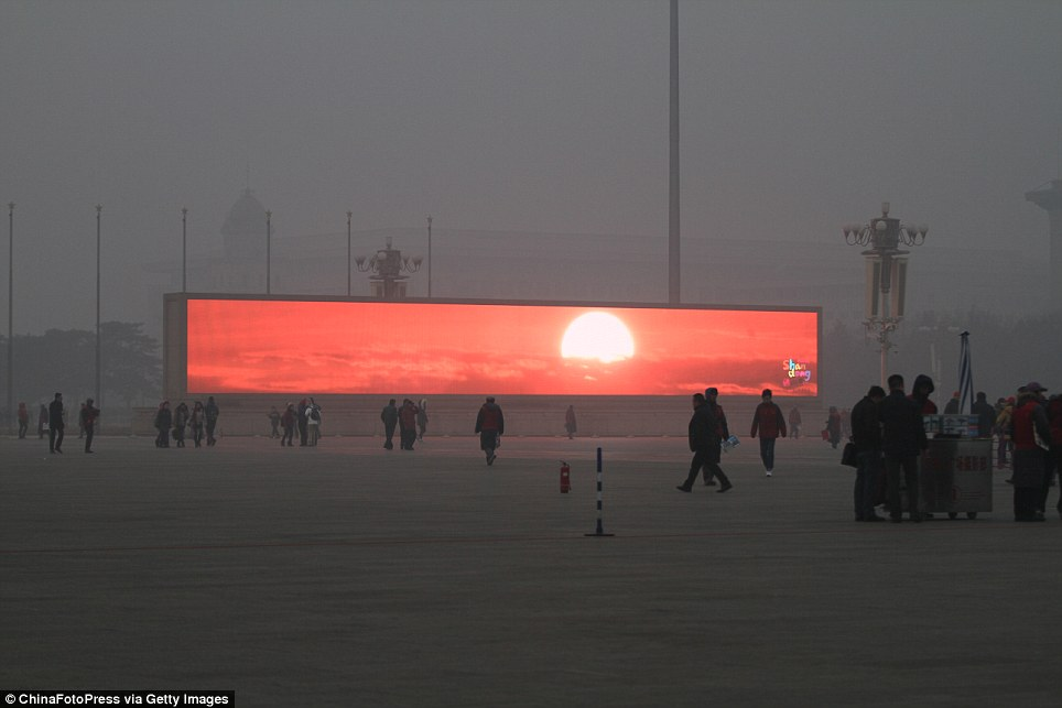 Virtual sunlight: The LED screen shows the rising sun in Tiananmen Square which is shrouded with heavy smog on January 16, 2014 in Beijing, China. Beijing Municipal Government issued a yellow smog alert this morning
