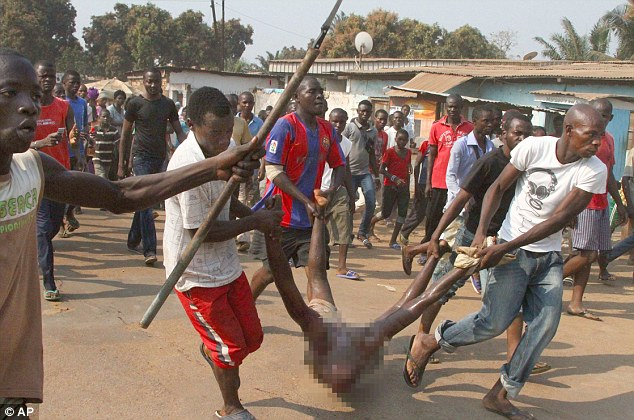 Men carry the body of a lynched Muslim man through a street in Bangui, Central African Republic, on Sunday