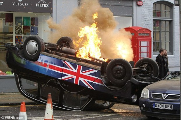 Up in flames! A London cab is flipped upside down and burns as cameras roll