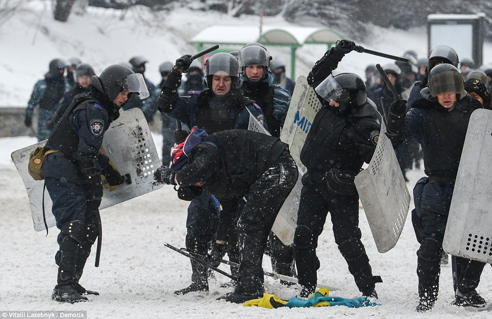 Brutal: Police troops beat a protester holding the national flag during anti-government protests in Kiev that are thought to have left three men dead