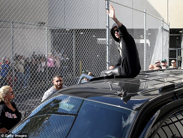 Waving to his fans: The icon sat on the roof of his waiting SUV as he looked at the crowd just after being released from jail on bail