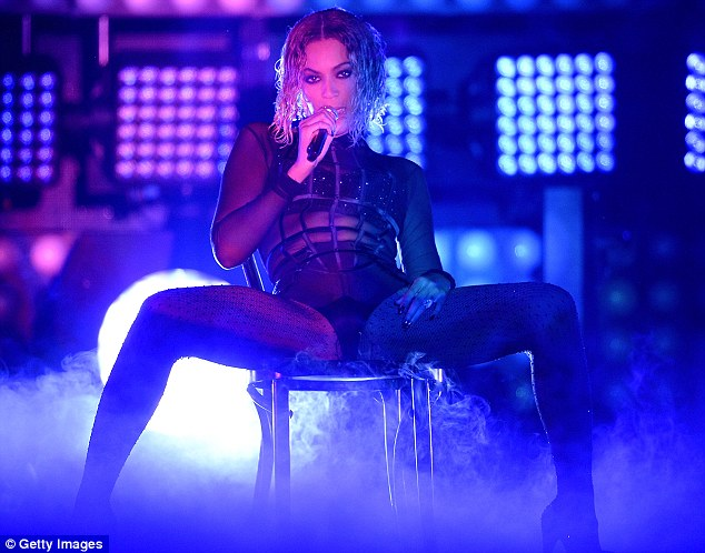 Kicking things off: The 32-year-old singer was bathed in blue light as she started the performance while straddling a chair