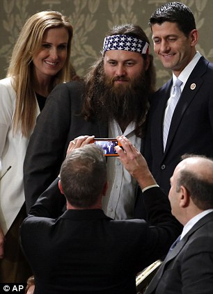 Selfies with a cable television star: Duck Dynasty's Willie Robertson, center and his wife Korie, pose with Rep. Paul Ryan, R-Wis., before President Barack Obama's State of the Union address on Capitol Hill