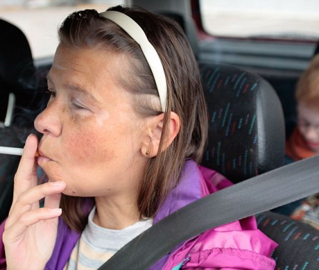 A Mother Smoking While Driving With Her Small Son In The Back Of Her Car