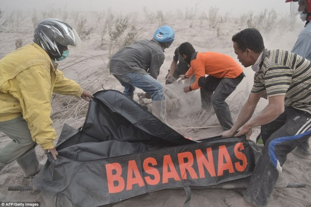 Harrowing: Rescue workers set about looking for bodies and survivors but their job was made more difficult by the intense heat, the dark and the threat of another eruption