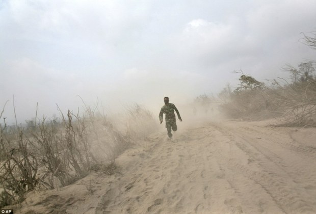 An Indonesian soldier runs on ash-covered road as he and his team search victims of the eruption of Mount Sinabung in Bekerah, North Sumatra, Indonesia