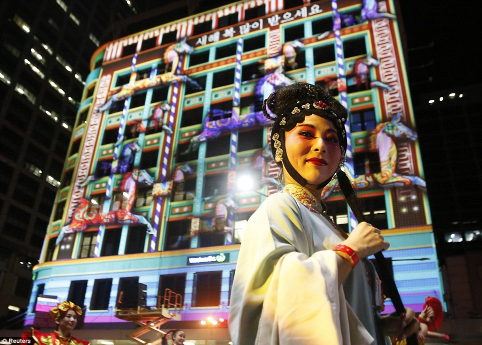 A performer walks past a building featuring projected images of horses to celebrate the beginning of the Year of the Horse during the Sydney celebrations