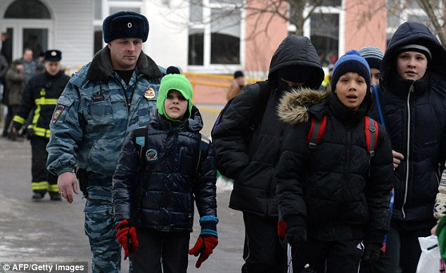 Evacuated: Pupils are escorted by a policeman out of their school north of Moscow