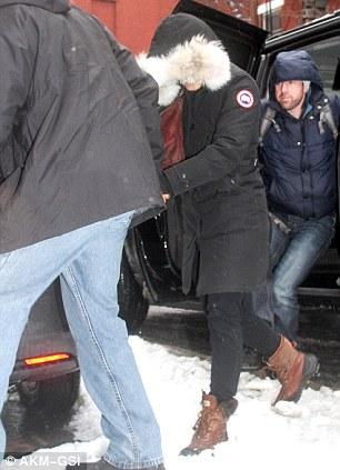 Snow: The estranged partner of Philip Seymour Hoffman, pictured left and right on Wednesday, trudged through the slushy snow in New York