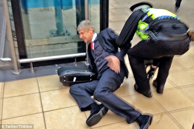 Helping hand: A police officer comes over to help Wenger back onto his feet