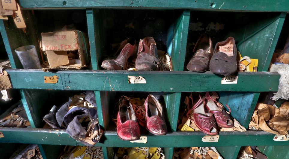 Dozens of pairs of workers' shoes sit in makeshift lockers on the site. The shoes appear to have already been in bad condition when they were left there 50 years ago