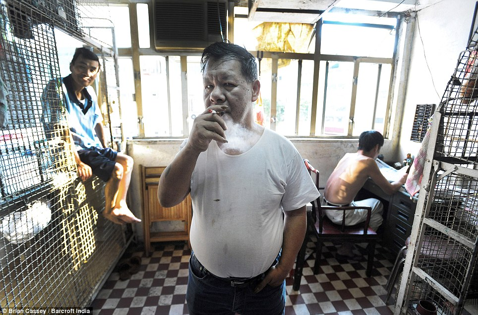 Hardship: Yan Chi Keung, 57, (centre), who suffers from mental illness, smokes in the room where he lives with several other men. The homes began in the 1950s