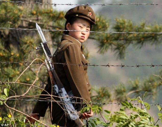 Menacing: North Korean dictator Kim Jong-un should face international justice for a catalogue of appalling crimes against humanity, UN investigators have. Above, a woman soldier at a camp in North Korea
