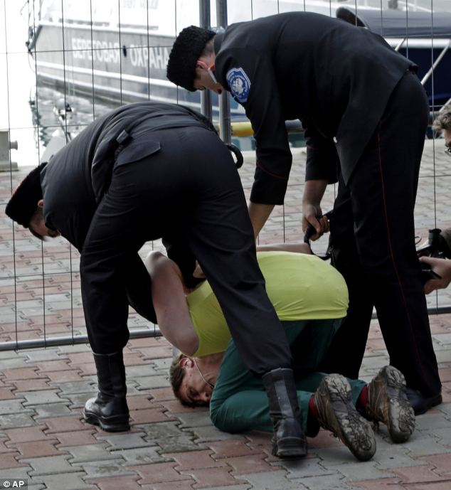 A member of Pussy Riot is restrained by Cossack militia. The group had gathered in a downtown Sochi restaurant, about 30km (21miles) from where the Winter Olympics are being held