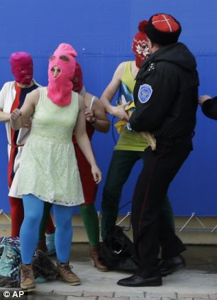 Members of the punk group Pussy Riot, including Maria Alekhina in the pink balaclava, center, are attacked