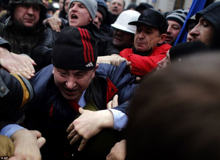 A suspected supporter of Ukraine's embattled president Viktor Yanukovych, center, is assaulted by anti-government protesters in Kiev