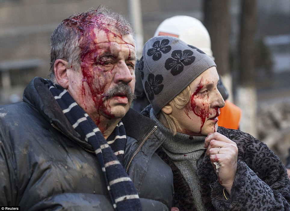 Wounded people are seen after clashes with riot police in central Kiev on February 18