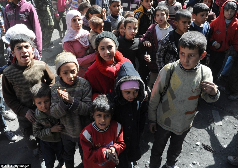 Long wait: Children await UN food parcels in Yarmouk, Damascus during a relief operation led by the UN agency for Palestinian refugees UNRWA