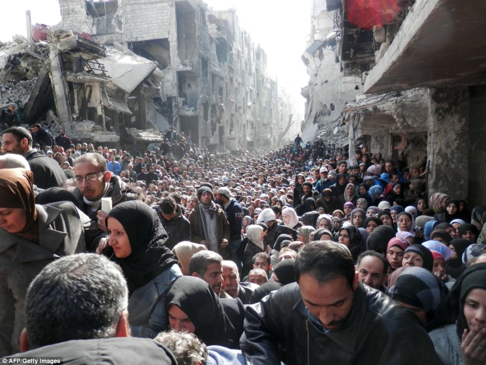 Hour of need: Residents of Syria's besieged Yarmuk Palestinian refugee camp, south of Damascus, crowding a destroyed street during a food distribution led by the UN agency