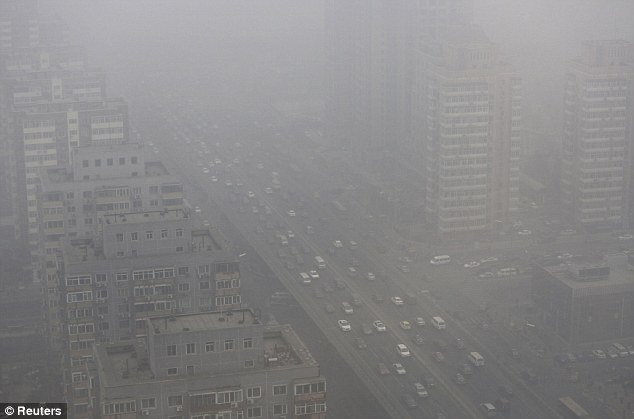 Pollution crisis: Cars can barely be seen through the smog as they drive along a road in Beijing today